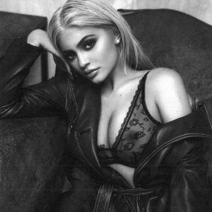 a blonde kylie jenner wearing a see through bra and showing off nipple ring